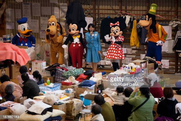 People dressed as Disney characters from the Tokyo Disney Resort greet evacuees at a centre for people effected by the March 11 tsunami and...