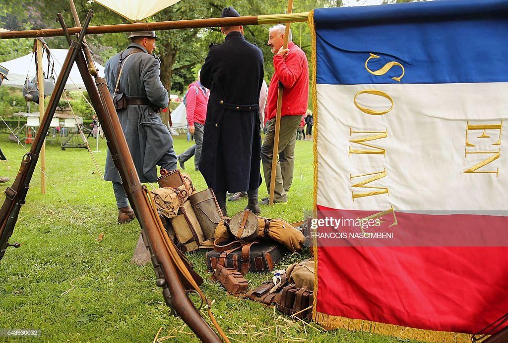 People dressed as French WWI soldiers stands near rifles and a French flag during a ceremony to commemorate the centenary of the battle of the Somme, one of the deadliest of the World War I (1.2 million killed, missing and wounded in five months), on June 30, 2016 in Albert, northern France. / AFP / FRANCOIS