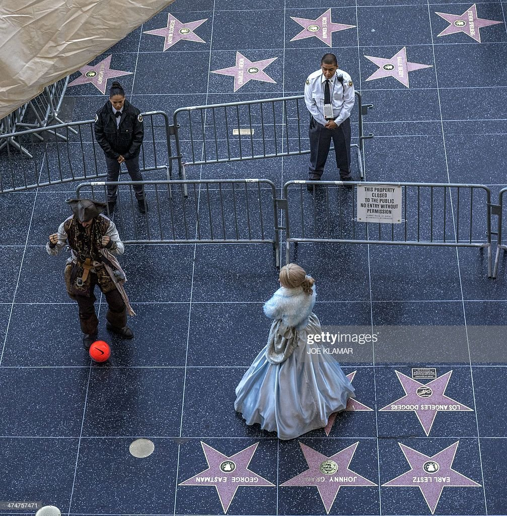 People dressed as Jack Sparrow and Cinderella perform in front of the guarded Dolby Theatre entrance during the preparations for the upcoming 86th...
