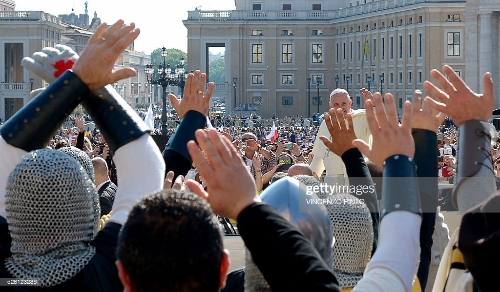 People dressed as Knights Templar wave at Pope Francis during his weekly general audience in Saint Peter's square at the Vatican on May 4, 2016. / AFP / VINCENZO