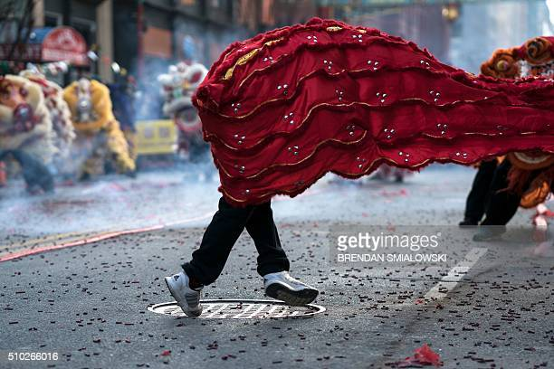 People dressed as lions and dragons dance through firecrackers to celebrate Chinese New Year in Chinatown February 14 2016 in Washington DC / AFP /...