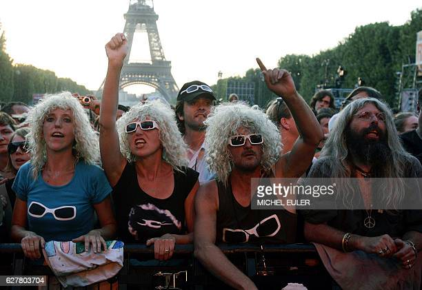 People dressed as Michel Polnareff attend the concert by the French singer in front of the Eiffel tower as part of the Bastille Day celebration 14...