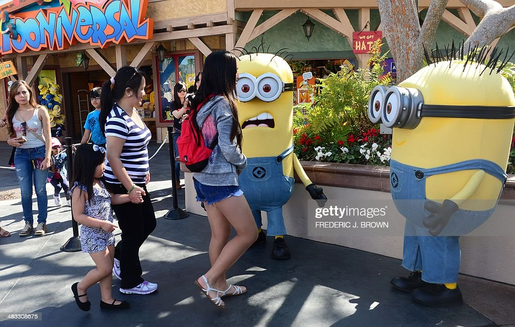 People dressed as Minions attract visitors at Universal Studios where the Despicable Me Minion Mayhem attraction was still under construction on...