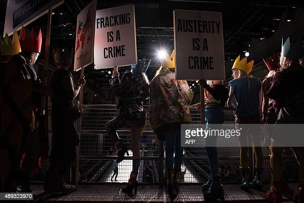People dressed as protestors prepare to take part in a flashmob ahead of a presentation by designer Vivienne Westwood at the Spring / Summer 2016...