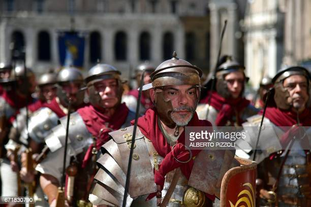 People dressed as Roman centurions walk past Italian soldiers during a parade to mark the anniversary of the foundation of Rome in 753 BC on April 23...