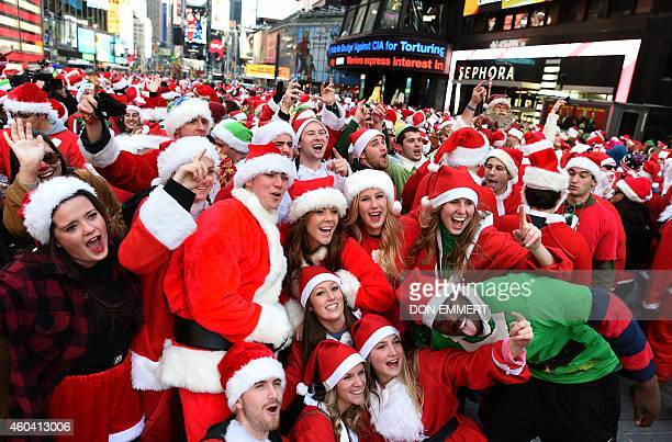 People dressed as Santa Claus and Mrs Claus pose in Times Square as they gather for the annual Santacon festivities on December 13 2014 in New York...