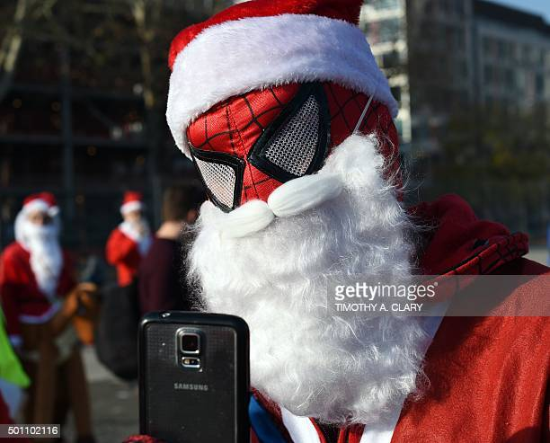 People dressed as Santa Claus gather in Brooklyn's McCarren Park during the SantaCon 2015 in New York City December 12 the 21st anniversary of the...