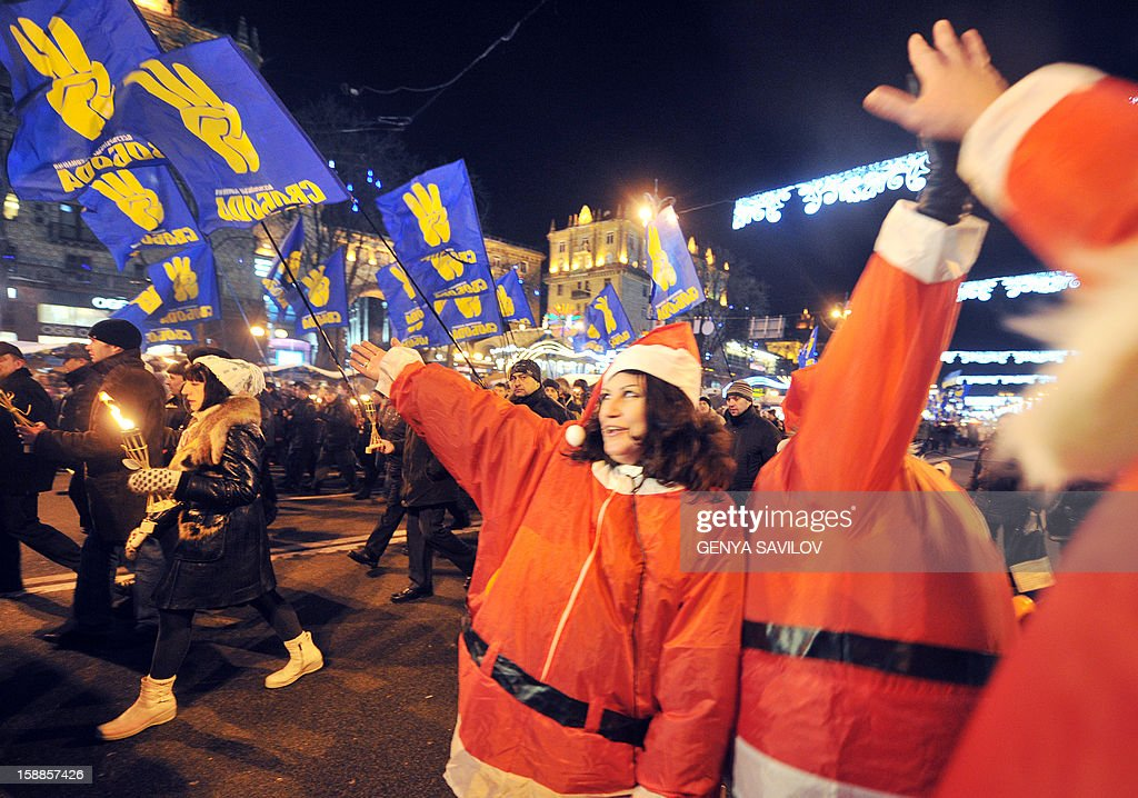 People dressed as Santa Clauses (R) react while nationalists march holding torches and flags in Kiev on January 1, 2013, as they mark the 104th anniversary of the birth of Stepan Bandera. Bandera was a Ukrainian politician and one of the leaders of Ukrainian national movement in western Ukraine, who headed the Organization of Ukrainian Nationalists (OUN). Bandera was an activist, a scout, and eventually the leader of the Ukrainian nationalist movement and was personally responsible for a series of terrorist acts against Polish and Ukrainian civilians committed in interwar Poland.