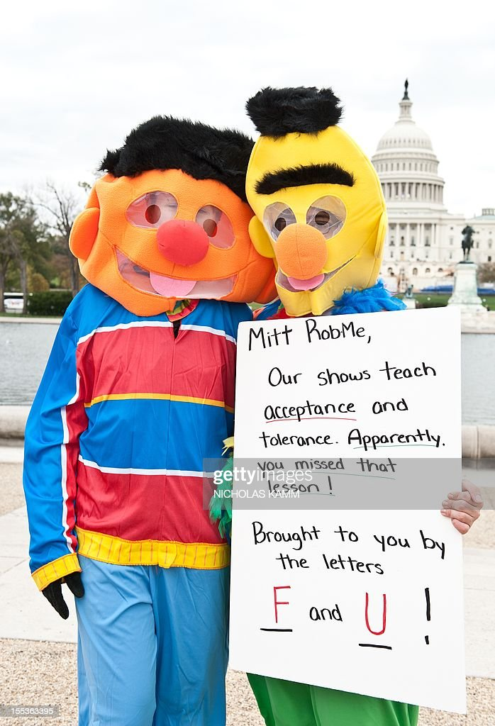 People dressed as Sesame Street characters Ernie and Bert hold a sign in support of public broadcasting during the 'Million Puppet March' in...
