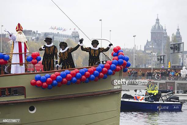 People dressed as Sinterklaas and his Zwarten Pieten helpers arrive in a boat during the traditional movein 'Intocht Sinterklaas' event in Amsterdam...