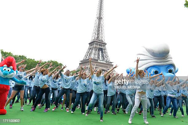 People dressed as smurfs take part in a flashmob leaded by choreographers of the French TV show 'Danse avec les Stars' during the 2nd edition of the...