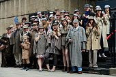 People dressed as the fictional detective created by the late Sir Arthur Conan Doyle Sherlock Holmes gather in central London on July 19 2014 as they...