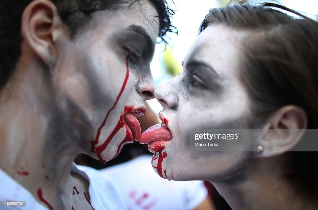 People dressed as vampires kiss while posing before a 'Zombie Walk' along Copacabana Beach during Day of the Dead festivities on November 2, 2013 in Rio de Janeiro, Brazil. Brazilians often mark the traditional Latin American holiday by visiting loved ones' graves while the Zombie Walk offers a modern twist.