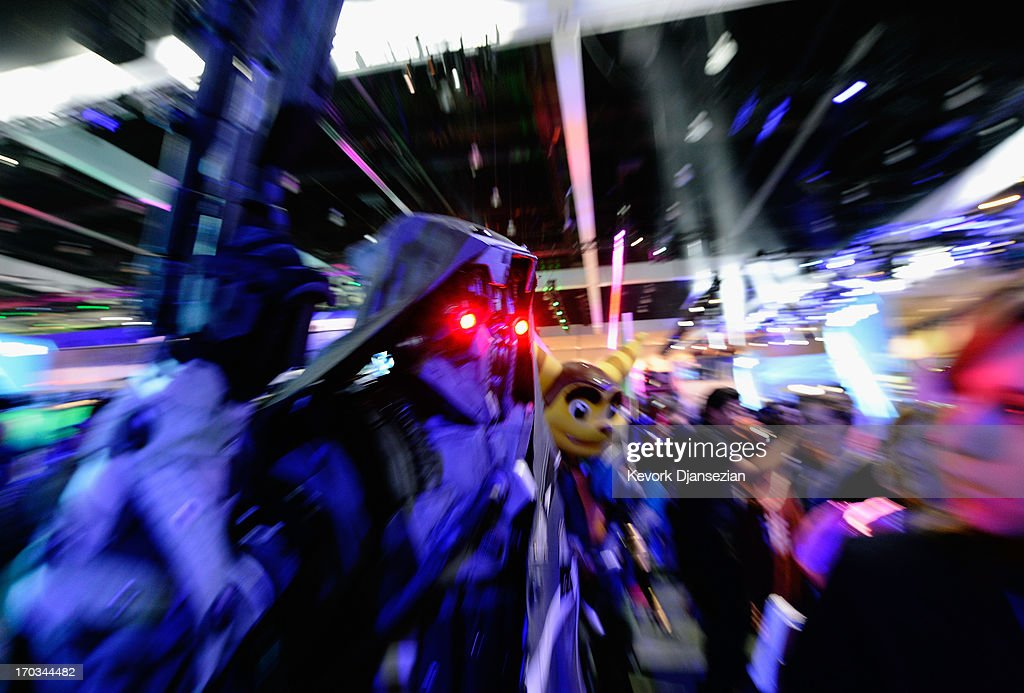 People dressed as video game characters walk in the Sony Playstation booth durng the Electronics Expo 2013 booth at the Los Angeles Convention Center on June 11, 2013 in Los Angeles, California. Thousands are expected to attend the annual three-day convention to see the latest games and announcements from the gaming industry.
