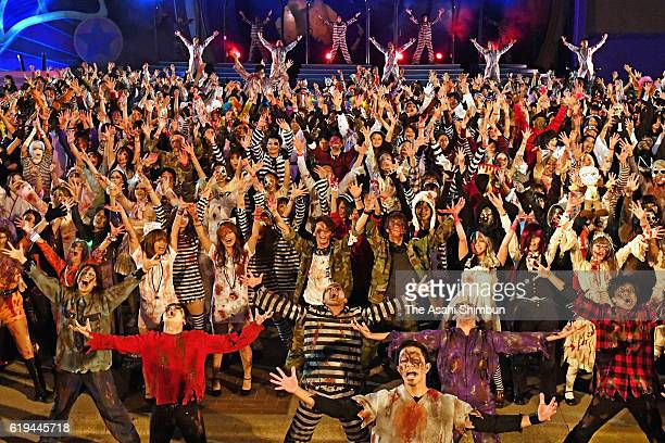 People dressed as zombie dance during a Halloween event at the Universal Studios Japan on October 31 2016 in Osaka Japan