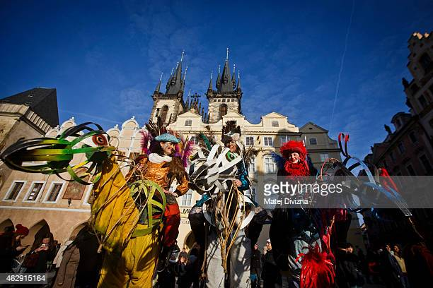 People dressed in costume sit on giant carnival figures during the opening of the Carnevale Praga 2015 festival as part of Prague carnival season at...