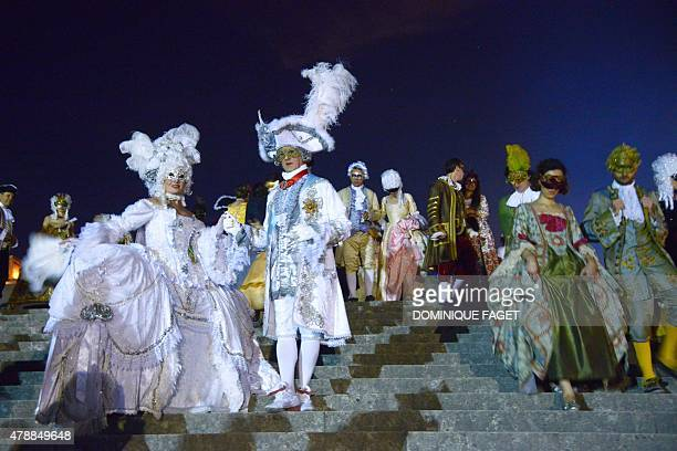 People dressed in costumes take part in the Grand Masked Ball on June 27 2015 at Chateau de Versailles in Versailles near Paris to mark the 300th...