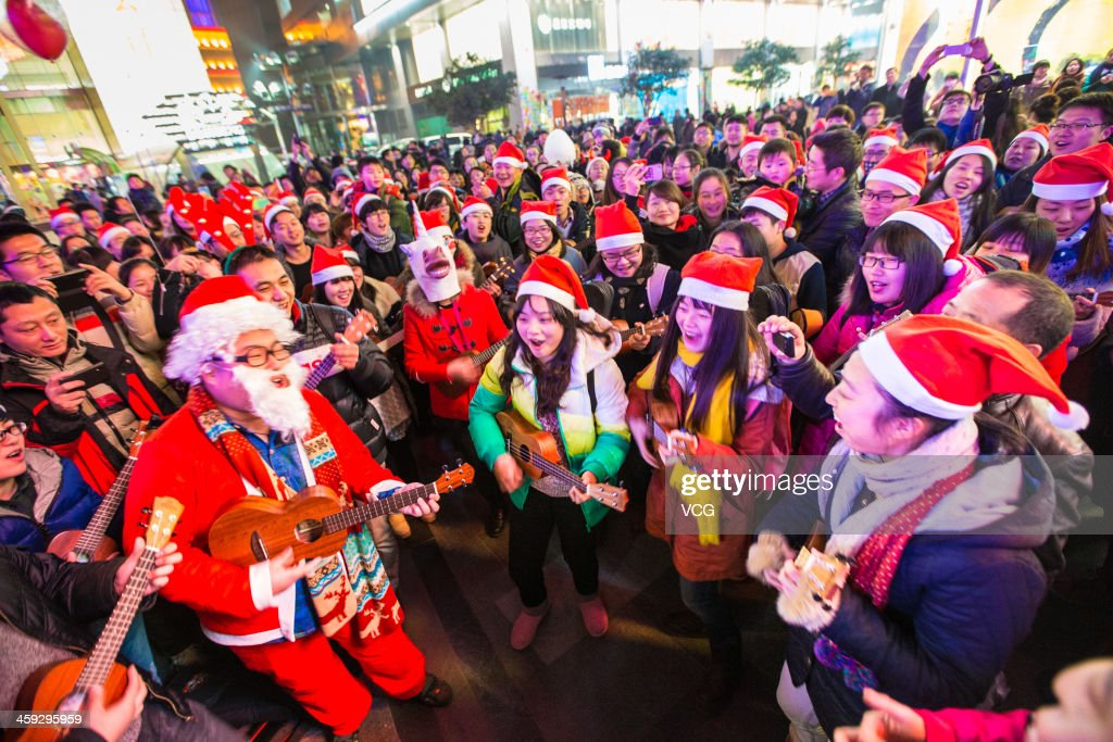 People dressed in Santa Claus costumes attend a celebration for the Christmas Eve at Xinjiekou on December 24, 2013 in Nanjing, China.