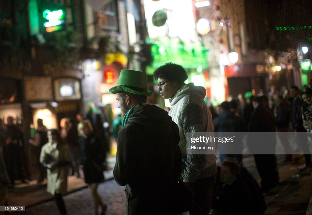 People dressed in St. Patrick's day colors walk through the Temple Bar area late at night in Dublin, Ireland, on Friday, March 15, 2013. Ireland's renewed competiveness makes it a beacon for the U.S. companies such as EBay, Google Inc. and Facebook Inc., which have expanded their operations in the country over the past two years. Photographer: Simon Dawson/Bloomberg via Getty Images