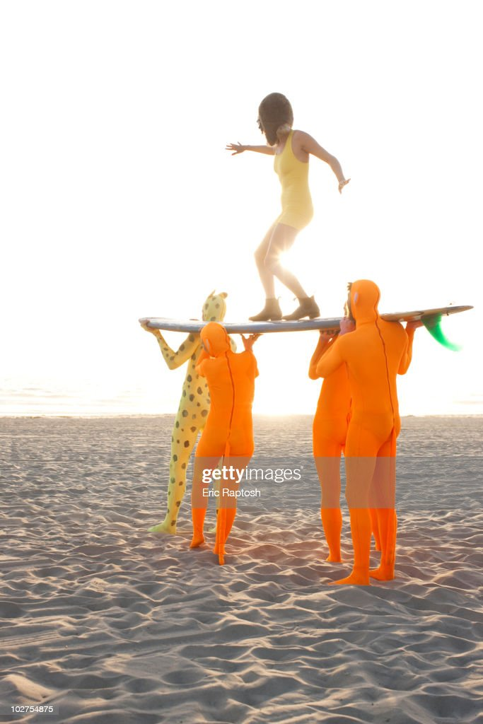 People dressed in strange costumes holding surfboard