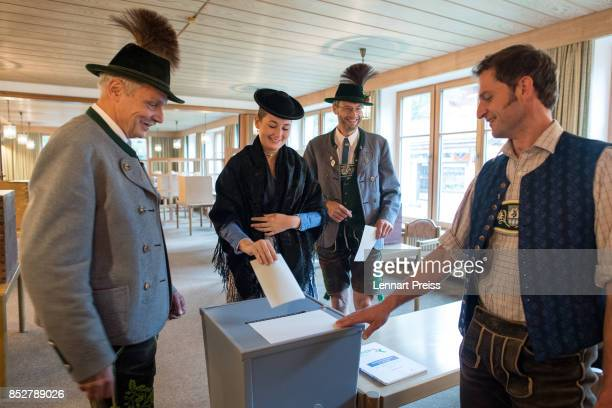 People dressed in traditional Bavarian clothes cast their election ballots at a polling station during German federal elections on September 24 2017...