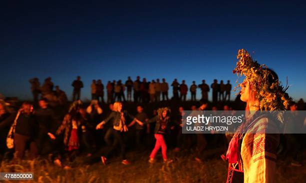 People dressed in traditional clothing celebrate Kupala Night near the light of a bonfire in the Village of Rakau some 30 km west of Minsk on June 27...