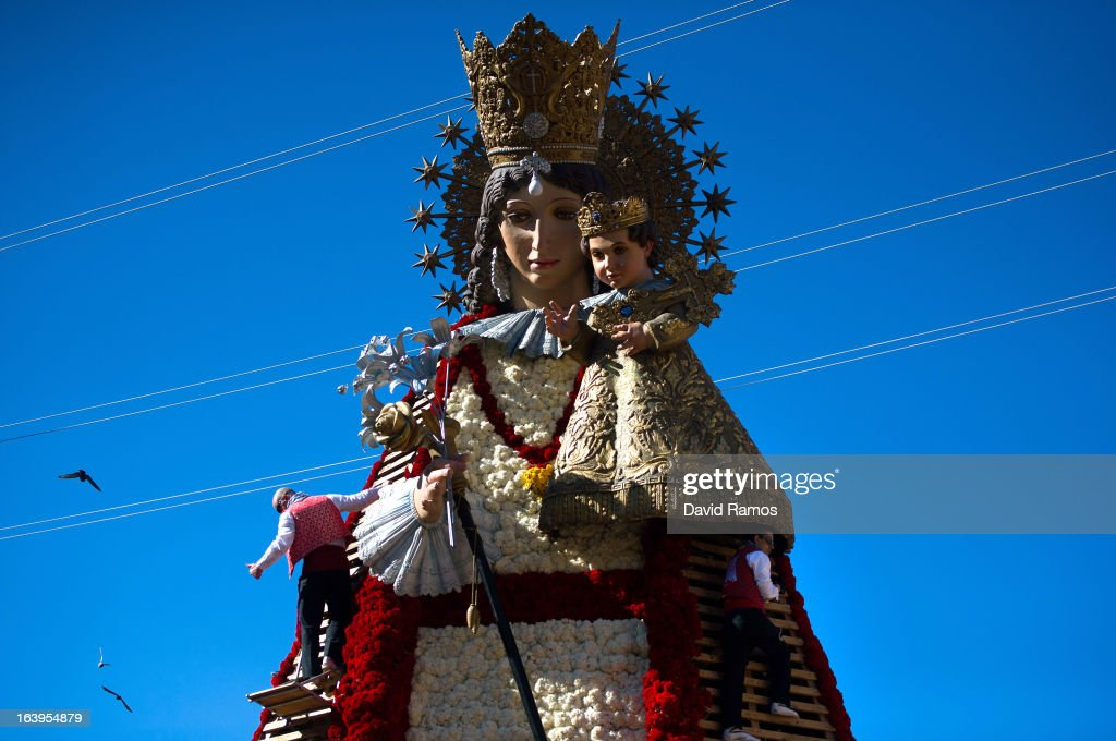 People dressed in traditional costume attach flowers onto a large model of Saint Mary on March 18, 2013 in Valencia, Spain. The Fallas festival, which runs from March 15 until March 19, celebrates the arrival of spring with fireworks, fiestas and bonfires made from large ninots (puppets).