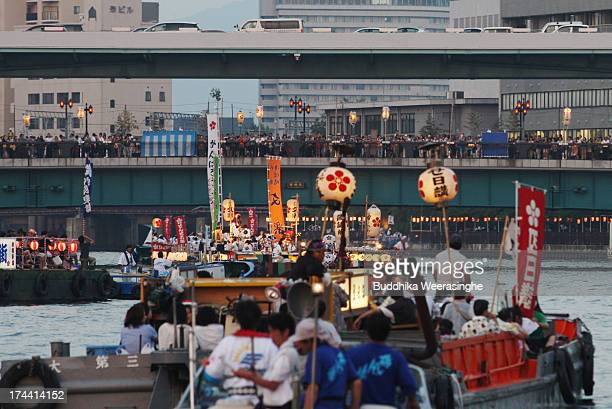 People dressed in traditional costume ride decorated boats along the Okawa river during the annual Tenjin summer festival boat parade on July 25 2013...