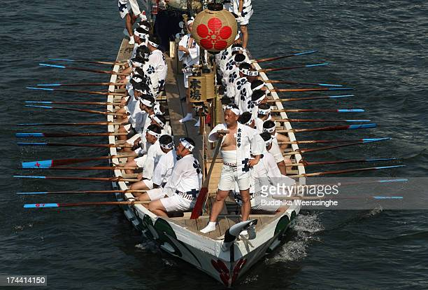People dressed in traditional costume row a boat along the Okawa river during the annual Tenjin summer festival boat parade on July 25 2013 in Osaka...