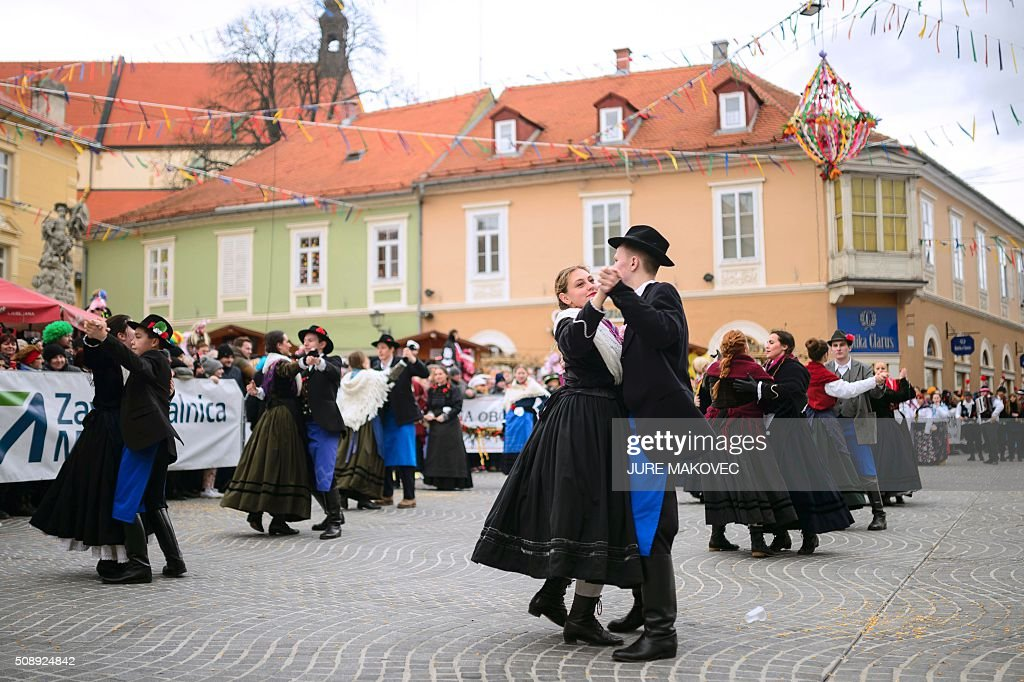 People dressed in traditional Slovenian costume dance during the Ptuj carnival parade in Ptuj, on February 7, 2016. The Ptuj carnival is the largest in Slovenia and last 11 days. / AFP / JURE MAKOVEC