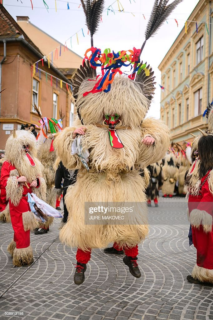 A person dressed in traditional Slovenian Kurent costumed dance during the Ptuj carnival parade in Ptuj, on February 7, 2016. Kurents are characters wearing sheep skin, a mask with a long red tongue, a cow bell, and multi-coloured ribbons on the head, intended to drive away evil spirits of the winter. The Ptuj carnival is the largest in Slovenia and last 11 days. / AFP / JURE MAKOVEC