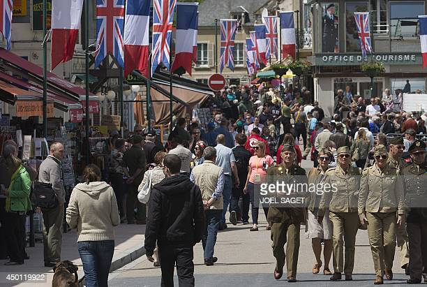 People dressed like British Worl War II soldiers walk in in Carentan Normandy on June 5 a dayd ahead of the DDay ceremonie The commemorations will...