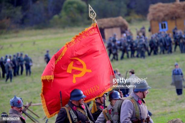 People dressed up as soldiers carry a flag of the Soviet Union in the reenactment of the events of October 1941 recreating an episode of the Battle...