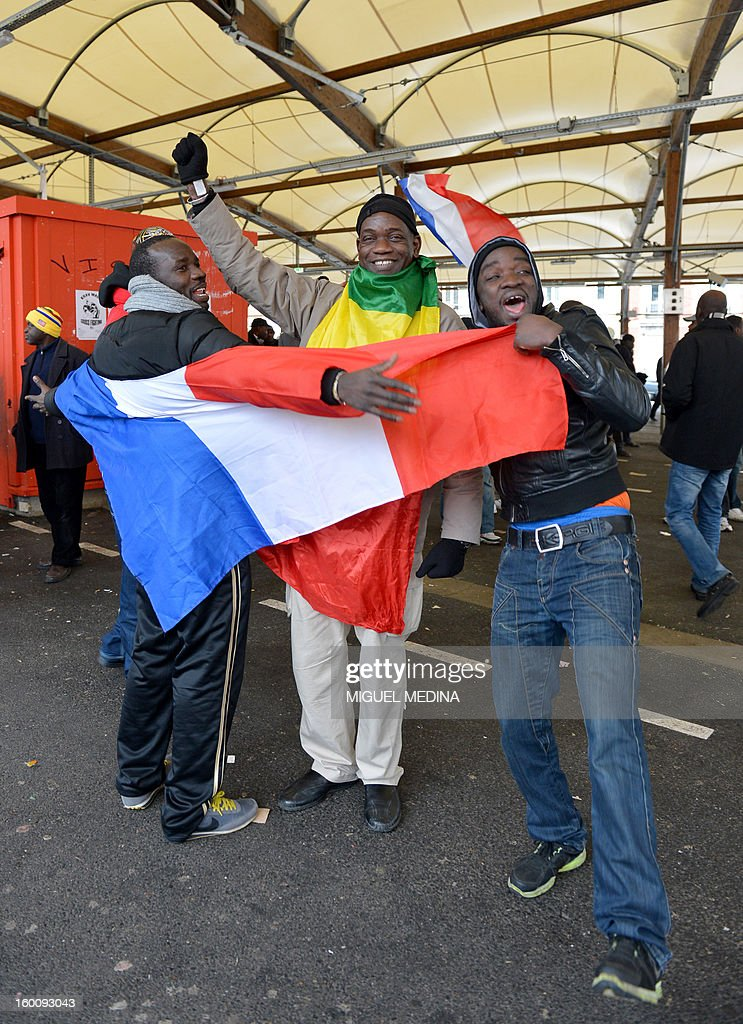 People dressed with Malian and French flags take part in a demonstration, organized by Malian associations, in support of the liberation forces of Mali on January 26, 2013 in Montreuil, near Paris. Placard reads 'For a united Mali, against terrorism'.