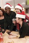 People drinking and wearing Santa hats at Christmas party