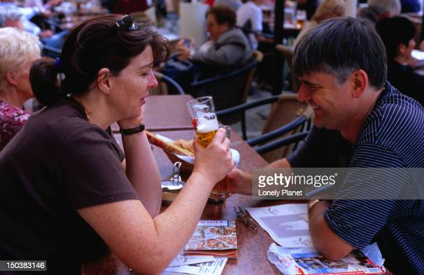 People drinking at an outdoor restaurant on the Old Town Square.