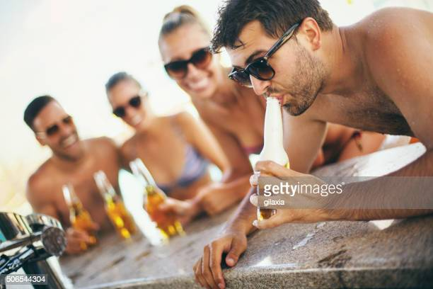 People drinking beer at beach bar.