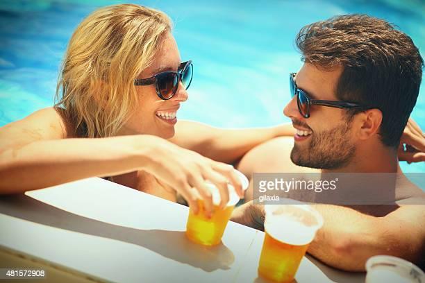 Gente beve birra in piscina.