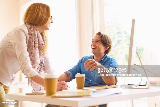 People drinking coffee and laughing in office