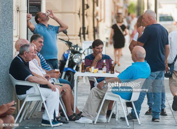 People drinks on the shaow of a bar to cool off from the heat on August 03 2017 in Reggio Calabria Italy An intense heatwave is sweeping across many...
