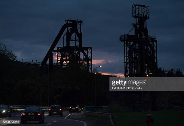 People drive cars at night on November 17 2016 next to the blast furnaces of the steel plant in Hayange eastern France / AFP / PATRICK HERTZOG