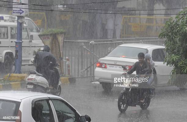 People drive during a rainfall on August 24 2014 in Indore India The city received 116 mm rainfall and the humidity oscillated between 47 and 91...