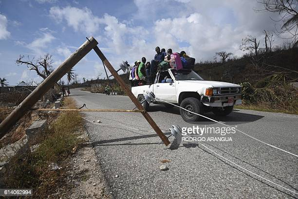 People drive in a car over a road damaged by Hurricane Matthew in Port Salut southwest of PortauPrince on October 11 2016 Haiti faces a humanitarian...