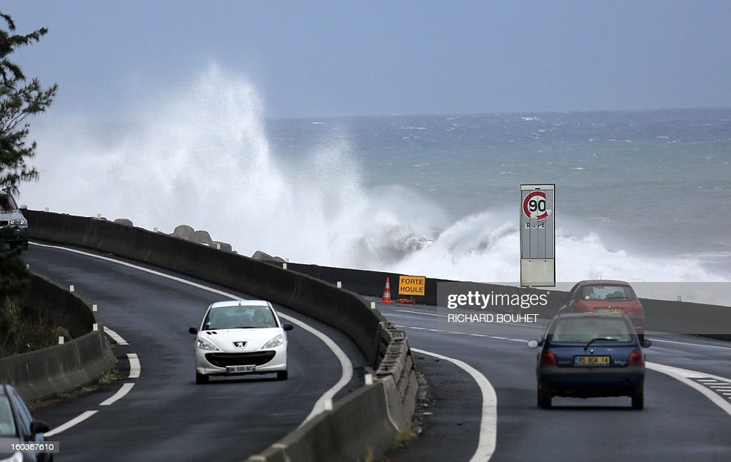 People drive on the North coast road of French Indian Ocean island of La Reunion on January 30, 2013 near Saint-Denis, as high waves hit the coastline. The cyclone Felleng was announced at 735 Km north of the island and progresses at the speed of 17 Km per hour. Felleng should approach the coast of the island from 300 km on February 1st.