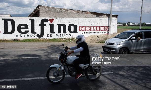 People drive past a wall painted with campaign publicity for Delfina Gomez the National Regeneration Movement's candidate for governor of the state...
