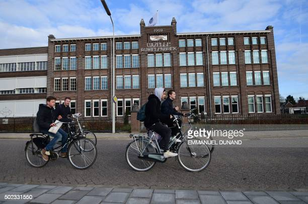 People drive past the factory building of Dutch bicycle manufacturer Gazelle in Dieren The Netherlands on December 10 2015 On the busy assembly line...