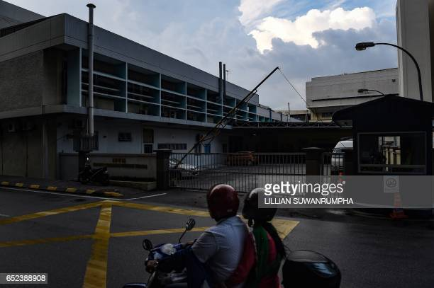 People drive past the forensics wing of the Hospital Kuala Lumpur where the body of Kim JongNam lies in Kuala Lumpur on March 12 2017 / AFP PHOTO /...
