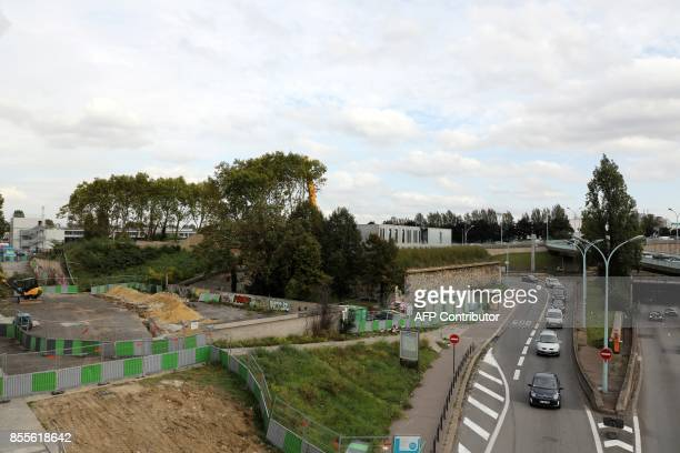 People drive vehicles by the underconstruction building that will host an accommodation centre for homeless people at Porte de Bercy in Paris on...