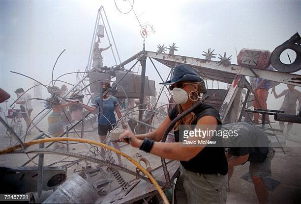 People drum on a percussion junk pile despite a blinding dust storm caused by strong winds September 2 2000 at the 15th annual Burning Man festival...