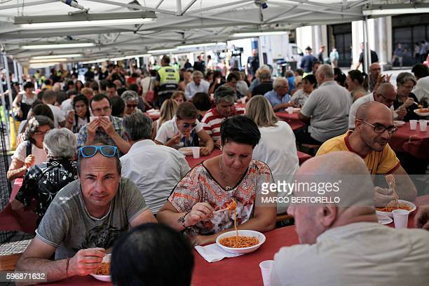 People eat a dish of spaghetti all'amatriciana during a charity event in Piazza San Carlo in Turin on August 28 whose profits are to help the...